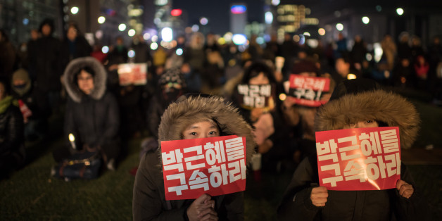 TOPSHOT - A woman hold a placard reading 'Arrest Park Geun-Hye' during a small rally following the impeachment of President Park Geun-Hye, in central Seoul on December 9, 2016.South Korean lawmakers voted to impeach President Park Geun-Hye, stripping away her sweeping executive powers over a corruption scandal and opening a new period of national uncertainty. / AFP / Ed JONES        (Photo credit should read ED JONES/AFP/Getty Images)