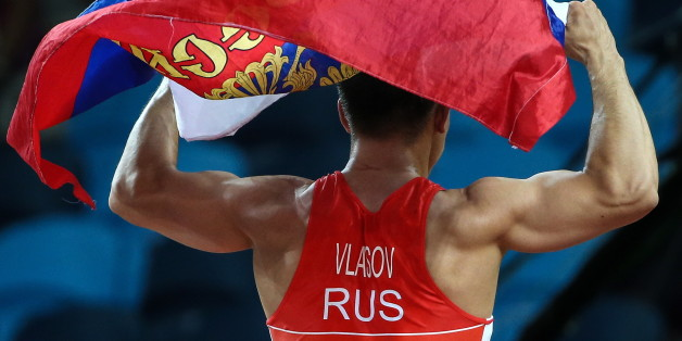 RIO DE JANEIRO, BRAZIL - AUGUST 14, 2016: Russia's Roman Vlasov waving his national flag after winning the men's -75kg wrestling final against Mark Overgaard Madsen of Denmark at the Rio 2016 Summer Olympic Games, at Carioca Arena 2. Valery Sharifulin/TASS (Photo by Valery Sharifulin\TASS via Getty Images)