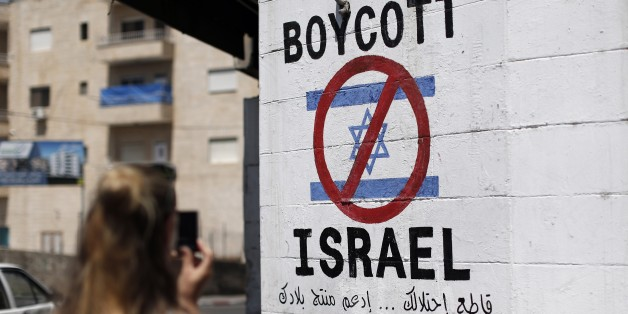 A tourist photographs a sign painted on a wall in the West Bank biblical town of Bethlehem on June 5, 2015, calling to boycott Israeli products coming from Jewish settlements. The international BDS (boycott, divestment and sanctions) campaign, that pushes for a ban on Israeli products, aims to exert political and economic pressure over Israel's occupation of the Palestinian territories in a bid to repeat the success of the campaign which ended apartheid in South Africa. AFP PHOTO / THOMAS COEX