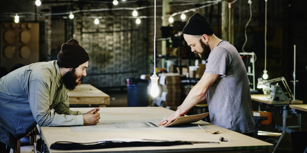 Two leatherworkers discussing product design at table in leather workshop