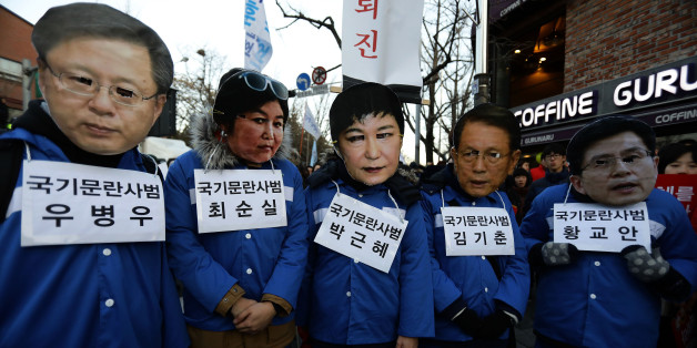 SEOUL, SOUTH KOREA - DECEMBER 10: Protesters wearing masks of South Korea's President Park Geun-Hye (R) and the president's long-time friend Choi Soon-Sil (L) walk during a rally against South Korean President Park Geun-Hye on December 10, 2016 in Seoul, South Korea. The South Korean National Assembly voted yesterday for an impeachment motion at its plenary session, which will set up the rare impeachment trial for President Park over the accusation of corruption involving Park and her long time