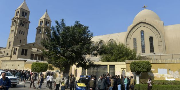 Egyptian security forces and onlookers gather outside the Saint Peter and Paul Coptic Orthodox Church (L), which is adjacent to the Saint Mark's Coptic Orthodox Cathedral (R), after it was hit by an explosion on December 11, 2016 in the Abbasiya neighbourhood in the capital Cairo. The bombing near the headquarters of the Coptic pope killed at least 25 people, state media reported. Copts, who make up about 10 percent of Egypt's population of 90 million, have faced persecution and discrimination that spiked during the 30-year rule of Hosni Mubarak, who was toppled by a popular uprising in 2011. / AFP / KHALED DESOUKI        (Photo credit should read KHALED DESOUKI/AFP/Getty Images)