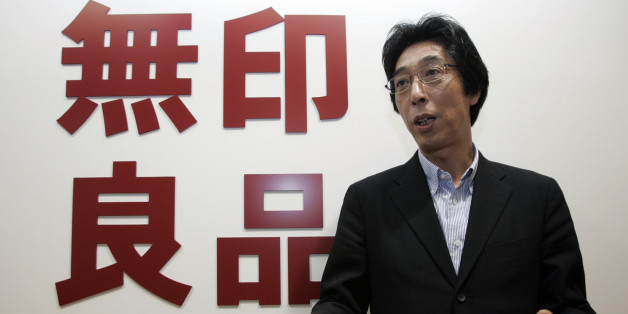 Japan's Ryohin Keikaku Co President Masaaki Kanai speaks during an interview next to the company's logo for its Muji retail chain, in Tokyo November 17, 2008. Ryohin Keikaku, which operates Muji stores, would find it hard to meet its full-year profit forecast given rapidly deteriorating consumer spending, Kanai said. REUTERS/Yuriko Nakao (JAPAN)
