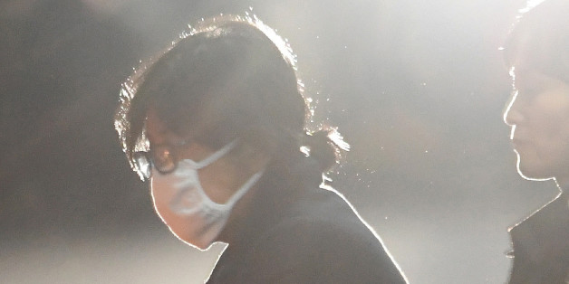 Choi Soon-Sil (L), the woman at the heart of a lurid political scandal engulfing South Korea's President Park Geun-Hye is escorted following her formal arrest, from the Central District Court in Seoul on November 3, 2016. A snowballing political scandal moved closer to embattled South Korean President Park Geun-Hye, with her newly nominated prime minister warning she could face a probe, hours after prosecutors detained a former presidential aide. / AFP / KOREA POOL / KOREA POOL        (Photo cre