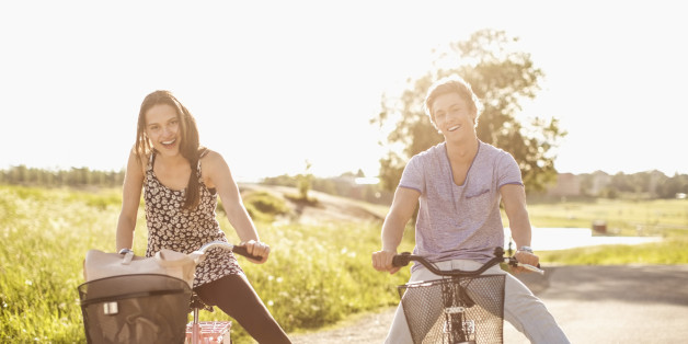 Portrait of happy young couple with legs apart cycling on country road