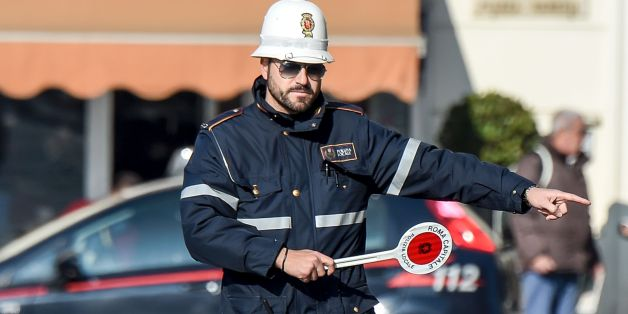 A police officer controls cars and scooters during the limited traffic day, in centeral Rome, on December 29, 2015. A second day with limited traffic of odd and even car plate numbers was enforced in the hope of lowering air pollution. A lack of rainfall has led pollution levels to climb in recent weeks, and has prompted the administration of Rome, to appeal to drivers to respect the rules.    / AFP / ANDREAS SOLARO        (Photo credit should read ANDREAS SOLARO/AFP/Getty Images)