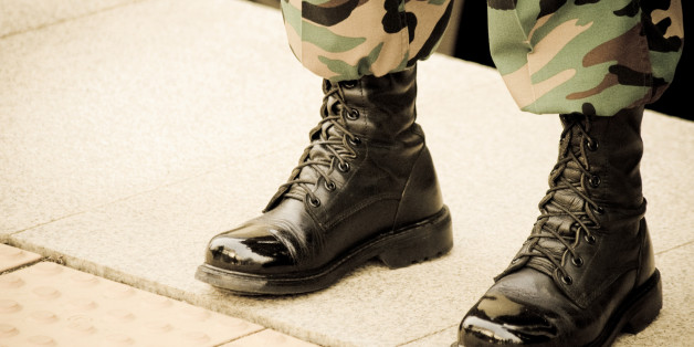 A solider in shiny boots stands at attention.