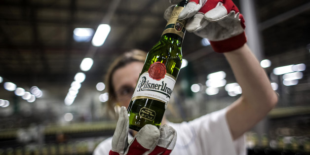 A worker holds up a bottle of beer against the light during a quality control inspection on the production line at the Pilsner Urquell brewery, operated by SABMiller Plc, in Plzen, Czech Republic, on Monday, Dec. 7, 2015. Carrying the Czech Beer label requires the use of specific types of Czech-grown barley and hops that give the domestic brew its characteristic bitterness, aroma and drinkability, said Vladimir Balach, the head of the Czech Beer and Malt Association in a 2014 interview. Photogra