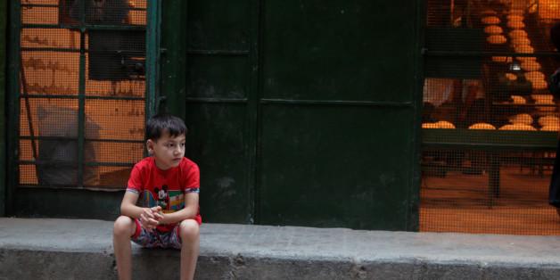 A boy sits outside a bakery in the rebel held al-Shaar neighbourhood of Aleppo, Syria July 14, 2016. REUTERS/Abdalrhman Ismail