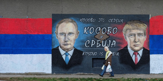 """A woman walks past a mural of U.S. president-elect Donald Trump and Russian President Vladimir Putin in Belgrade, Serbia, December 4, 2016. The text on the mural reads in Russian, Serbia and English """"Kosovo is Serbia"""".  REUTERS/Marko Djurica"""