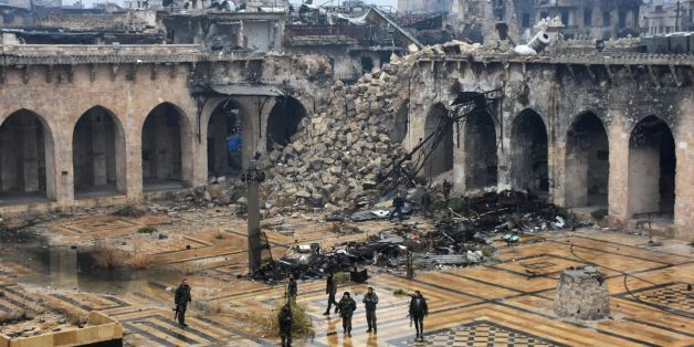 TOPSHOT - A general view shows Syrian pro-government forces walking in the ancient Umayyad mosque in the old city of Aleppo on December 13, 2016, after they captured the area.After weeks of heavy fighting, regime forces were poised to take full control of Aleppo, dealing the biggest blow to Syria's rebellion in more than five years of civil war. / AFP / George OURFALIAN        (Photo credit should read GEORGE OURFALIAN/AFP/Getty Images)