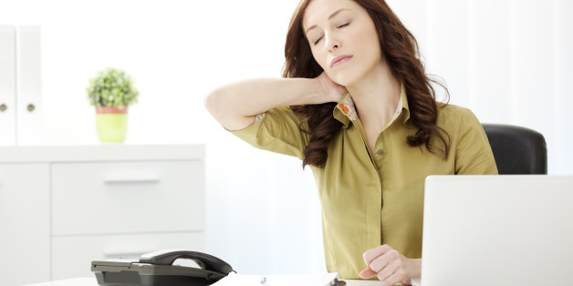 Young Businesswoman Having Neckache in the office, doing massage of the neck and sitting at the desk.