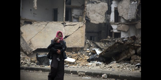 Syrians leave a rebel-held area of Aleppo towards the government-held side on December 13, 2016 during an operation by Syrian government forces to retake the embattled city.UN chief Ban Ki-moon expressed alarm over reports of atrocities against civilians Monday, as the battle for Aleppo entered its final phase with Syrian government forces on the verge of retaking rebel-held areas of the city. / AFP / KARAM AL-MASRI        (Photo credit should read KARAM AL-MASRI/AFP/Getty Images)