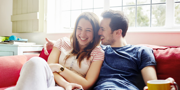 Young couple laugh together as they relax on sofa