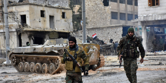 Syrian pro-government forces patrol the northern city of Aleppo on December 14, 2016. Shelling and air strikes sent terrified residents running through the streets of Aleppo as a deal to evacuate rebel districts of the city was in danger of falling apart. / AFP / George OURFALIAN        (Photo credit should read GEORGE OURFALIAN/AFP/Getty Images)