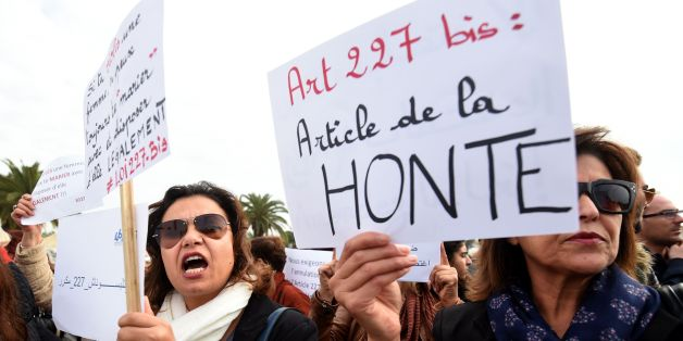 Tunisian women hold placards during a demonstration against the article 227 bis of the penal code on December 14, 2016, outside the Assembly of the Representatives of the People in Tunis, after a Tunisian court has approved the marriage of a 13-year-old girl to a relative who made her pregnant.Under Tunisian law, sex with a girl under 15 without the use of force is punishable by six years in prison, but the culprit can halt proceedings by marrying the victim. / AFP / FETHI BELAID        (Photo c
