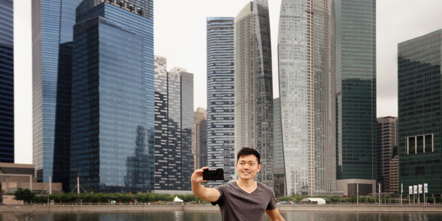 A man in casual clothes takes his own photos against the Singapore skyline with a smart phone