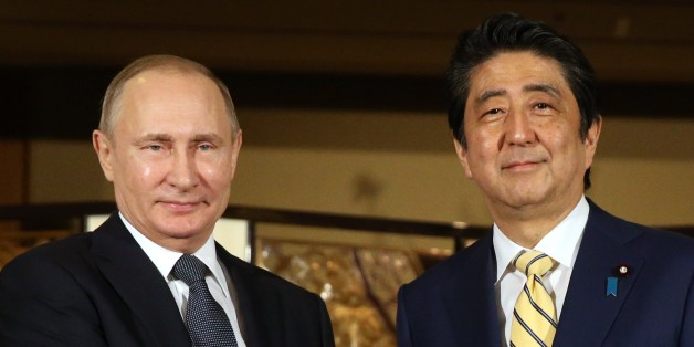 JAPAN, NAGATO - DECEMBER  15: (RUSSIA OUT) Russian President Vladimir Putin (L) shakes hands with Japanese Prime Minister Shinzo Abe (R) during the official reception ceremony on December 15, 2016  in Nagato, Japan. The Russian president is on a two-days visit to Japan. (Photo by Mikhail Svetlov/Getty Images)