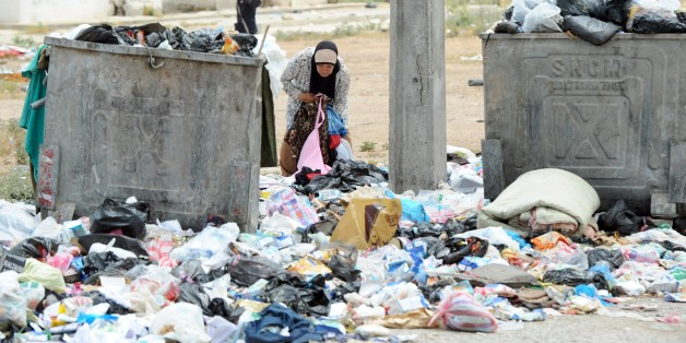GO WITH STORY BY MARINE MESSINA - A woman inspects uncollected rubbish poured on the ground on May 27, 2014 in El Agba, north of the Tunisian capital, Tunis. Fed up with the dirt and the inefficiency of the authorities, volonteers and citizens have launched several initiatives to clear up their neighborhoods. AFP PHOTO / FETHI BELAID        (Photo credit should read FETHI BELAID/AFP/Getty Images)