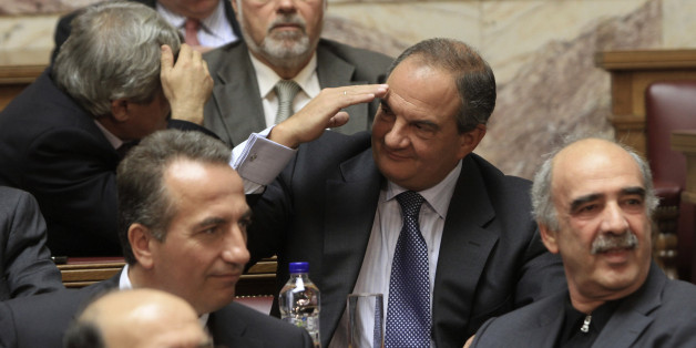 Former conservative Prime Minister Costas Karamanlis (C) greets a colleague during a New Democracy party parliamentary group meeting in Athens November 2, 2011.    REUTERS/Panagiotis Tzamaros  (GREECE - Tags: POLITICS BUSINESS)