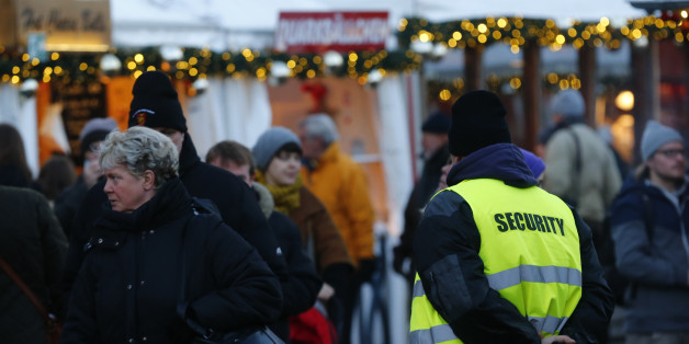 A security officer watches people visiting the Gendarmenmarkt Christmas market on the first day of its opening in Berlin, Germany, November 23, 2015. The security measures in public places were increased after recent deadly attacks in Paris. REUTERS/Hannibal Hanschke