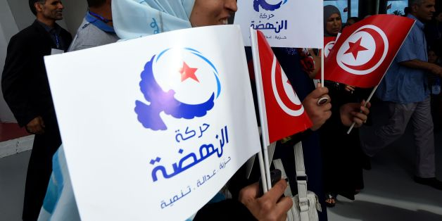 Supporters of Tunisia's Islamist Ennahdha Party wave the national and party flags on May 20, 2016 during the opening of Ennahdha's three-day congress in Tunis. Thousands of people attended the opening ceremony of the congress -- the first since 2012 -- held at a sports complex in Rades, south of the capital Tunis, amid heavy police security. / AFP / FETHI BELAID        (Photo credit should read FETHI BELAID/AFP/Getty Images)