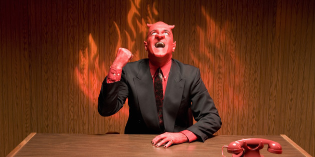 Businessman dressed as devil laughing