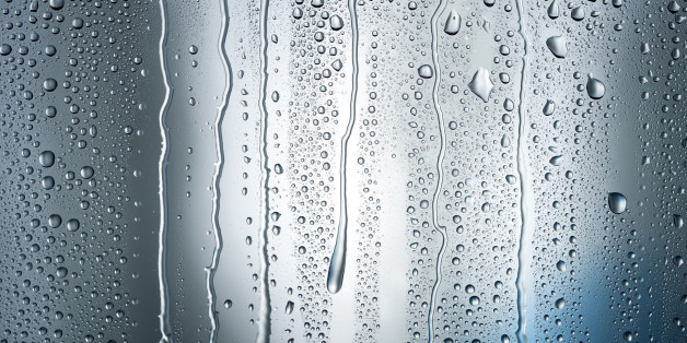 Heavy condensation forms droplets and streams of water running down a dark blue shadowy background