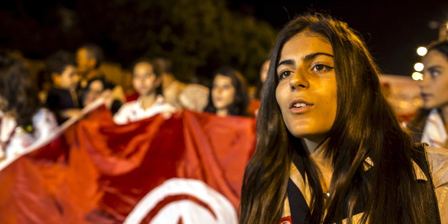 A woman attends a protest to condemn an attack by a gunman at the beach of the Imperial Marhabada  hotel in Sousse, Tunisia, June 27, 2015. Tour companies were evacuating thousands of foreign holidaymakers from Tunisia on Saturday, a day after a gunman killed 39 people as they lounged at the beach in an attack claimed by Islamic State. Tunisia's Prime Minister Habib Essid said most of the dead were British, and its health ministry said eight Britons, a German, a Belgian and an Irish citizen were