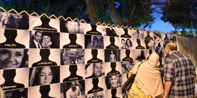 Egyptians look at posters of the 66 victims of the EgyptAir MS804 flight that crashed in the Mediterranean Sea, as they take part in a march near the Cairo Opera House in the Egyptian capital in honour of them on May 26, 2016.Investigators are still searching for the Airbus A320's two black boxes on the seabed as they seek answers as to why the aircraft came down early on May 19, with 66 people on board. / AFP / KHALED DESOUKI        (Photo credit should read KHALED DESOUKI/AFP/Getty Images)