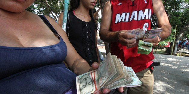 People exchange money to buy good in Cucuta, Colombia, before crossing the Francisco de Paula Santander international bridge, linking Urena, in Venezuela and Cucuta, in Colombia, despite the border closing order issued by the Venezuelan government, on December 17, 2016.President Nicolas Maduro had ordered the 100-bolivar unit to be scrapped -to combat what he called a US-backed plot against Venezuela- and scheduled to start releasing new higher-denomination notes. He ordered the Colombia border