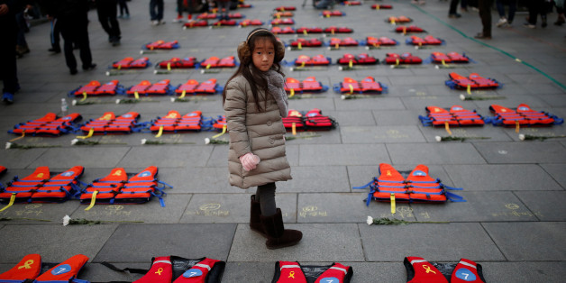 A girl stands between life vests symbolising the 304 victims of sunken ferry Sewol during a protest demanding South Korean President Park Geun-hye's resignation in Seoul, South Korea December 17, 2016.  REUTERS/Kim Hong-Ji