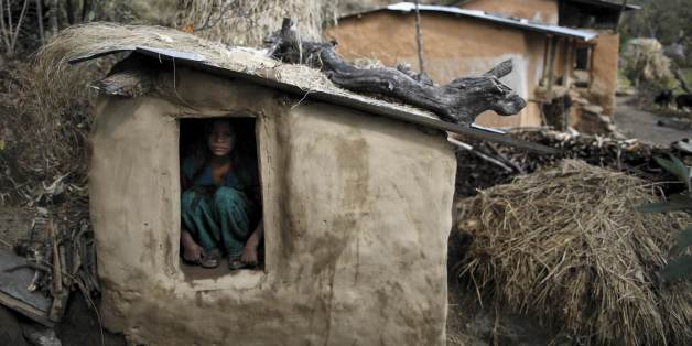 Uttara Saud, 14, sits inside a Chaupadi shed in the hills of Legudsen village in Achham District in western Nepal in this February 16, 2014 file picture. Chaupadi is the practice of treating women as impure and untouchable when they menstruate. In isolated regions like Achham, chaupadi has been a custom for centuries. But those from Nepal's cities or from abroad often don't know what it means. When women go through their monthly cycle, they are not allowed to enter a house or pass by a temple. T