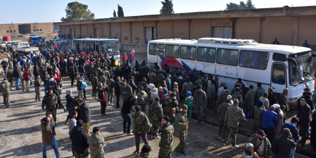 Syrians who were evacuated from Fuaa and Kafraya,two Shiite villages under rebel-siege on the northern outskirts of Idlib are welcomed by pro-government forces as they arrive in Jibrin on the eastern outskirts of Aleppo on December 19, 2016.  / AFP / George OURFALIAN        (Photo credit should read GEORGE OURFALIAN/AFP/Getty Images)