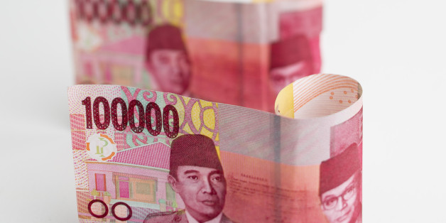 Indonesian 100,000 rupiah banknotes are arranged for a photograph in Bangkok, Thailand, on Tuesday, Sept. 15, 2015. Indonesia is preparing a major overhaul of financial safety regulations to guard against the potential for bank collapses. Indonesian banks are facing slower loan growth and a weakening economy at a time when the Federal Reserve is preparing to lift U.S. interest rates, a move that has the potential to create more disruption in emerging markets. Photographer: Brent Lewin/Bloomberg