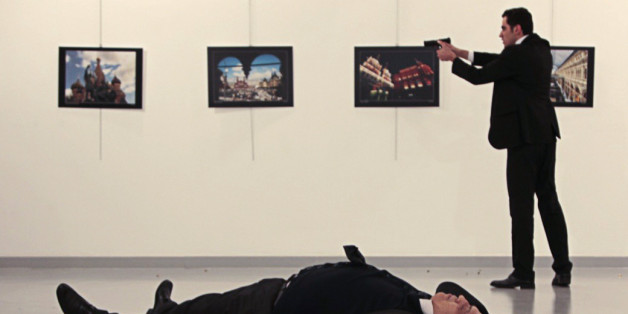 EDITORS NOTE: Graphic content / This picture taken on December 19, 2016 shows Andrey Karlov (bottom), the Russian ambassador to Ankara, lying on the floor after being shot by a gunman (R) during an attack during a public event in Ankara. A gunman crying 'Aleppo' and 'revenge' shot Karlov while he was visiting an art exhibition in Ankara on December 19, witnesses and media reports said. The Turkish state-run Anadolu news agency said the gunman had been 'neutralised' in a police operation, without giving further details. / AFP / Hurryet / Hasim KILIC / Turkey OUT        (Photo credit should read HASIM KILIC/AFP/Getty Images)