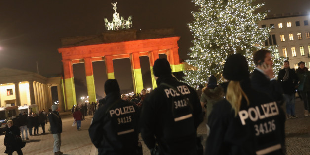 BERLIN, GERMANY - DECEMBER 20:  The Brandenburg Gate stands illuminated in the colors of the German flag as police walk past the day after a truck drove into a crowded Christmas market in the city center on December 20, 2016 in Berlin, Germany. So far 12 people are confirmed dead and 45 injured. Authorities have confirmed they believe the incident was an attack and have arrested a Pakistani man who they believe was the driver of the truck and who had fled immediately after the attack. Among the dead are a Polish man who was found on the passenger seat of the truck. Police are investigating the possibility that the truck, which belongs to a Polish trucking company, was stolen yesterday morning.  (Photo by Sean Gallup/Getty Images)