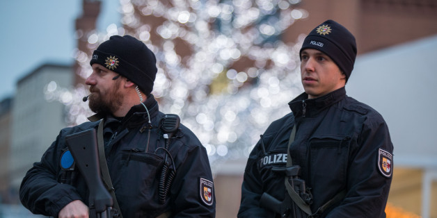 Armed policemen stand at the christmas market in Schwerin, northern Germany, on December 20, 2016 one day after a truck crashed into a Christmas market in Berlin.Twelve people were killed and almost 50 wounded, 18 seriously, when the lorry tore through the crowd on December 19, 2016, smashing wooden stalls and crushing victims, in scenes reminiscent of July's deadly attack in the French Riviera city of Nice. / AFP / dpa / Jens Büttner / Germany OUT        (Photo credit should read JENS BUTTNE