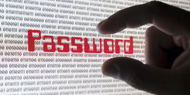 A male hand grabbing the word 'PASSWORD' on a computer screen with binary code.