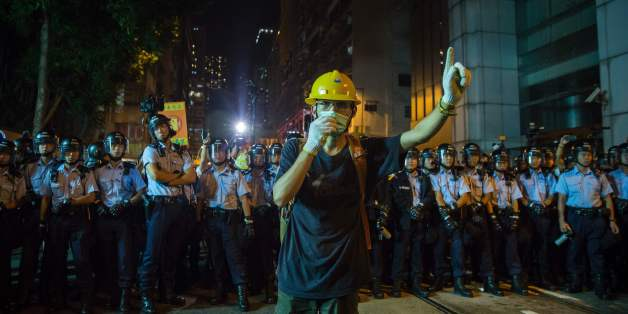 A protester wearing a mask gestures in front of riot police amid ongoing demonstrations in Hong Kong on November 6, 2016.Hong Kong police used pepper spray November 6 to drive back hundreds of protesters angry at China's decision to intervene in a row over whether two pro-independence lawmakers should be barred from the city's legislature. In chaotic scenes reminiscent of mass pro-democracy protests in 2014, demonstrators charged metal fences set up by police outside China's liaison office in th