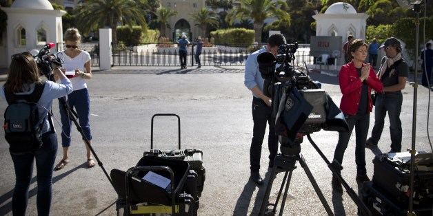 Journalists stand in front of the Riu Imperial Marhaba Hotel in Port el Kantaoui, on the outskirts of Sousse south of the capital Tunis, on June 27, 2015, in the aftermath of a shooting attack on the beach resort claimed by the Islamic State group. The IS group on June 27 claimed responsibility for the massacre in the seaside resort that killed nearly 40 people, most of them British tourists, in the worst attack in the country's recent history. AFP PHOTO / KENZO TRIBOUILLARD        (Photo credit should read KENZO TRIBOUILLARD/AFP/Getty Images)