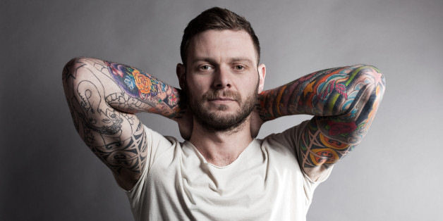 Brunette male, showing tattoo sleeves, with hands on his neck, on a grey background.