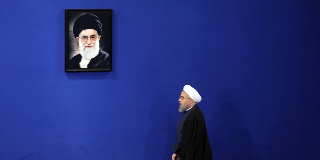 Iranian President Hassan Rouhani walks past a portrait of Iranian supreme leader Ayatollah Ali Khamenei as he arrives to give a speech during a press conference in the capital Tehran on August 29, 2015. AFP PHOTO / ATTA KENARE        (Photo credit should read ATTA KENARE/AFP/Getty Images)