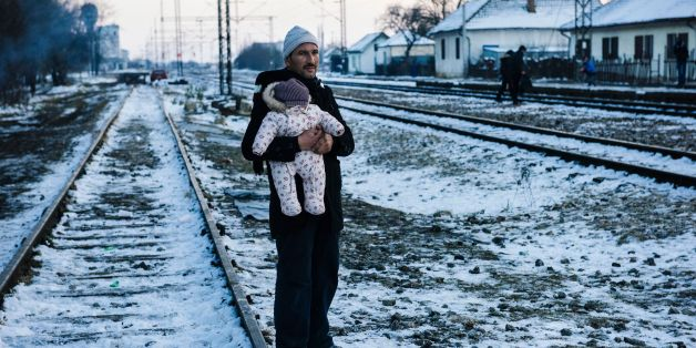 TOPSHOT - A man holds his baby while waiting with other migrants and refugees at a train station for a train in southern Serbian town of Presevo on January 20, 2016. As refugees continued to flow from Greece through the Balkans on their way to western Europe, aid workers sounded alarms over inadequate shelter from the current freezing temperatures and snowy conditions, particularly for children.  / AFP / DIMITAR DILKOFF        (Photo credit should read DIMITAR DILKOFF/AFP/Getty Images)