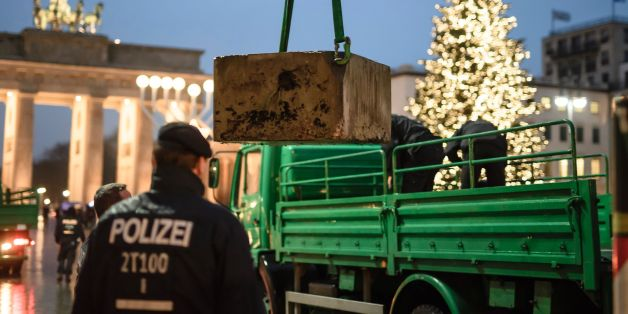 Policemen install a concrete barricade near the Brandenburg Gate in Berlin on December 22, 2016.