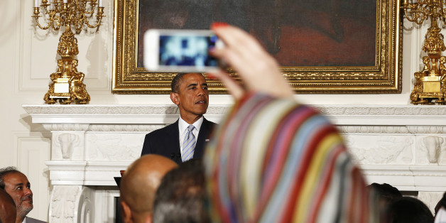 A Muslim woman takes a photo as U.S. President Barack Obama speaks while hosting an Iftar dinner at the White House in Washington July 14, 2014. Iftar is the meal after sunset that breaks the day of fasting during Ramadan. REUTERS/Kevin Lamarque  (UNITED STATES - Tags: POLITICS RELIGION)