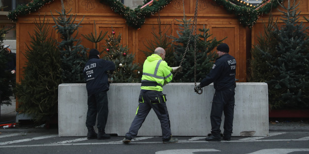 BERLIN, GERMANY - DECEMBER 22:  Police install concrete blocks as a security barrier on the periphery of the reopened Breitscheidplatz Christmas market, where three days ago a truck plowed into the market, killed 12 people and injured dozens in a terrorist attack on December 22, 2016 in Berlin, Germany. The Breidscheidplatz Christmas market is reopening today, though its small amusement rides and bright lights displays will remain shut off in a sign of continuing mourning for the attack victims. Meanwhile police have launched a European-wide manhunt for Anis Amri, a 24-year-old Tunisian man they suspect of having driven the truck.  (Photo by Sean Gallup/Getty Images)