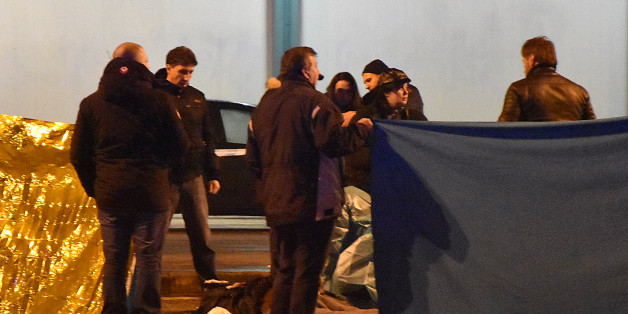 Italian police and forensics experts gather around the body of suspected Berlin truck attacker Anis Amri after he was shot dead in Milan on December 23, 2016.  The Tunisian man suspected of carrying out the deadly Berlin truck attack at the Christmas market was shot dead by police in Milan on December 23, Italy's interior minister Marco Minniti said. The minister told a press conference in Rome that Anis Amri had been fatally shot after firing at two police officers who had stopped his car for a