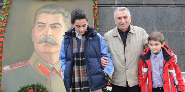 The grandson of Joseph Stalin (Dzhugashvili), Yevgeny Dzhugashvili (C) poses with his grandsons Josef Vissarionovitch Dzhugashvili (L) and Vaso Dzhugashvili (R) next to the portrait of their famous relative in the central square of Gori, some 80 kilometers from Tbilisi on December 21, 2009.  People pay tribute to Joseph Stalin 130 years after his birth, with debate still raging in the country over the reputation of a leader seen in the West as an evil tyrant. While historians blame Stalin for the deaths of millions in purges, prison camps and forced collectivization, many in Russia still praise him for leading the Soviet Union to victory over Nazi Germany in World War II.      AFP PHOTO/ VANO SHLAMOV (Photo credit should read VANO SHLAMOV/AFP/Getty Images)
