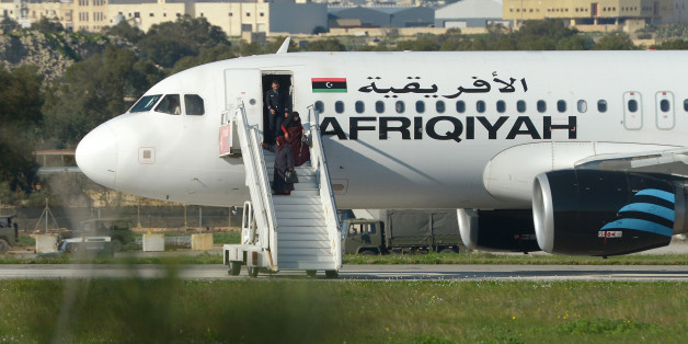 A picture taken on December 23, 2016 shows a group of hostages being released in Valletta, Malta, from the Afriqiyah Airways A320 after it was hijacked from Libya.A man who said he was armed with a grenade hijacked a Libyan plane which landed on Malta Friday with 118 people on board, Malta's prime minister and government sources on the Mediterranean island said. After more than an hour on the tarmac, the plane's door opened and a first group of women and children were seen descending a mobile st